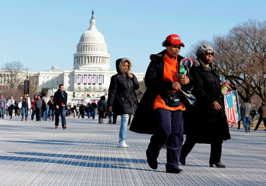 Barbara Whittaker, center, and Fran Willis, right, both of Richton Park, Ill., walk on the National Mall Sunday, Jan. 20, 2013,with the U.S. Capitol prepared for the ceremonial swearing-in of President Barack Obama, the 57th Presidential Inaugural on Monday in Washington. (AP Photo/Alex Brandon) Photo: Alex Brandon, Associated Press / AP