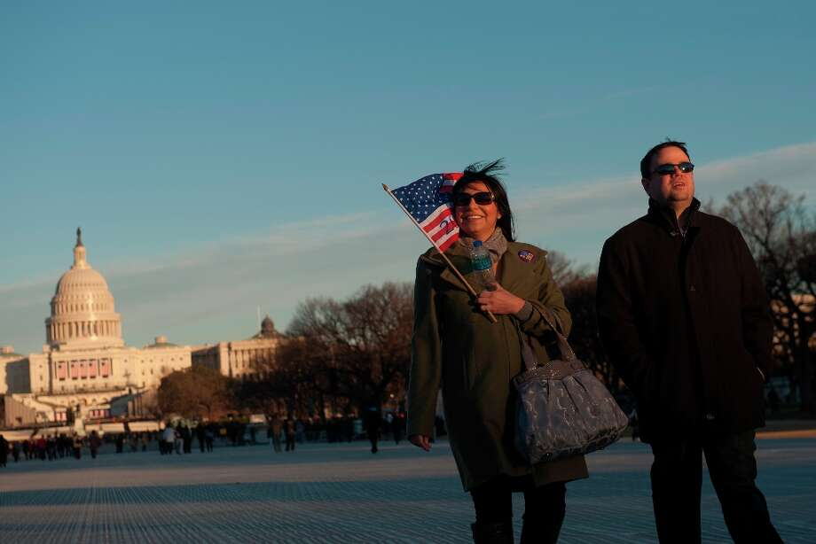 Christine Cortez, of Los Angeles, left, holds a U.S. flag while standing with Kevin Snowden, of Virginia, in front of the Capitol building ahead of the presidential inauguration in Washington, D.C., U.S., on Sunday, Jan. 20, 2013. As he enters his second term U.S. President Barack Obama has shed the aura of a hopeful consensus builder determined to break partisan gridlock and adopted a more confrontational stance with Republicans. Photo: Daniel Acker, Bloomberg / © 2013 Bloomberg Finance LP