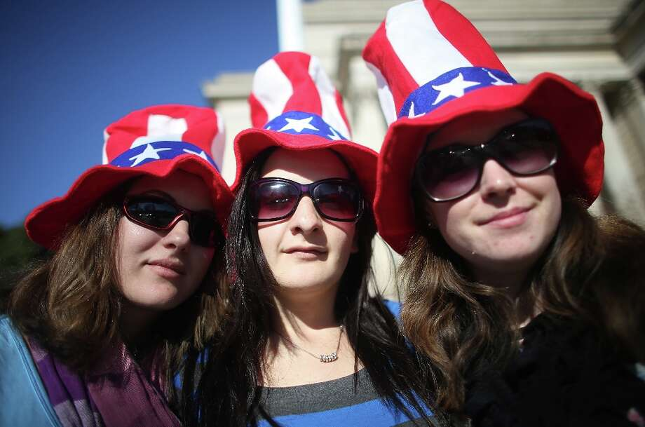 (L to R) Bek Russell, Jane Heard and Emma Llewellyn, tourists from Australia, pose while sporting Uncle Sam hats as Washington prepares for U.S. President Barack Obama's second inauguration on January 20, 2013 in Washington, DC.  One day before the public inaugural ceremony at the U.S. Captiol on January 21, Obama was officially sworn in for his second term during a private ceremony surrounded by friends and family in the Blue Room of the White House. Photo: Mario Tama, Getty Images / 2013 Getty Images