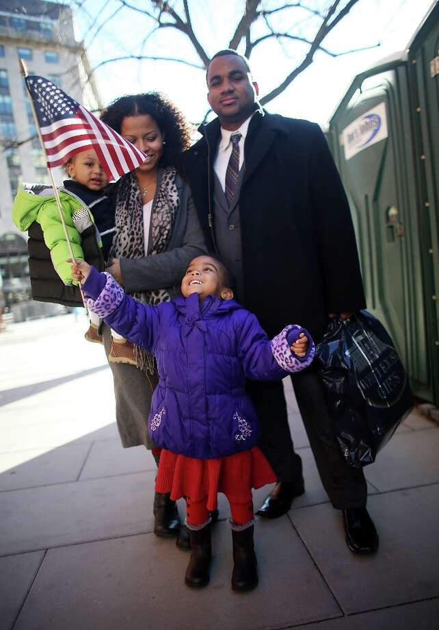 Ariana Smith holds an American flag as mother Ana Blanco-Smith carries Christian Smith and father Grasford Smith poses during preparations for U.S. President Barack Obama's second inauguration on January 20, 2013 in Washington, DC. The U.S. capital is preparing for the second inauguration of U.S. President Barack Obama, which will take place on January 21. Photo: Mario Tama, Getty Images / 2013 Getty Images