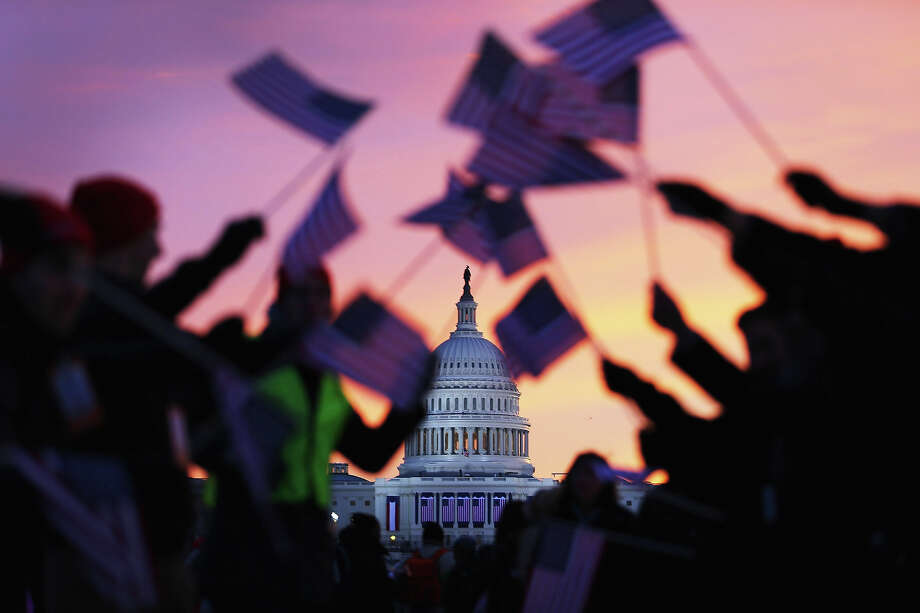 WASHINGTON, DC - JANUARY 21:  People wave American flags as people gather near the U.S. Capitol building on the National Mall for the Inauguration ceremony on January 21, 2013 in Washington, DC.  U.S. President Barack Obama, will be ceremonially sworn in for his second term today. Photo: Joe Raedle, Getty Images / 2013 Getty Images