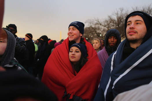 WASHINGTON, DC - JANUARY 21: Brandon Adamski and Alicia Burke keep warm in a blanket as they and others gather near the U.S. Capitol building on the National Mall for the Inauguration ceremony on January 21, 2013 in Washington, DC.  U.S. President Barack Obama, will be ceremonially sworn in for his second term today. Photo: Joe Raedle, Getty Images / 2013 Getty Images