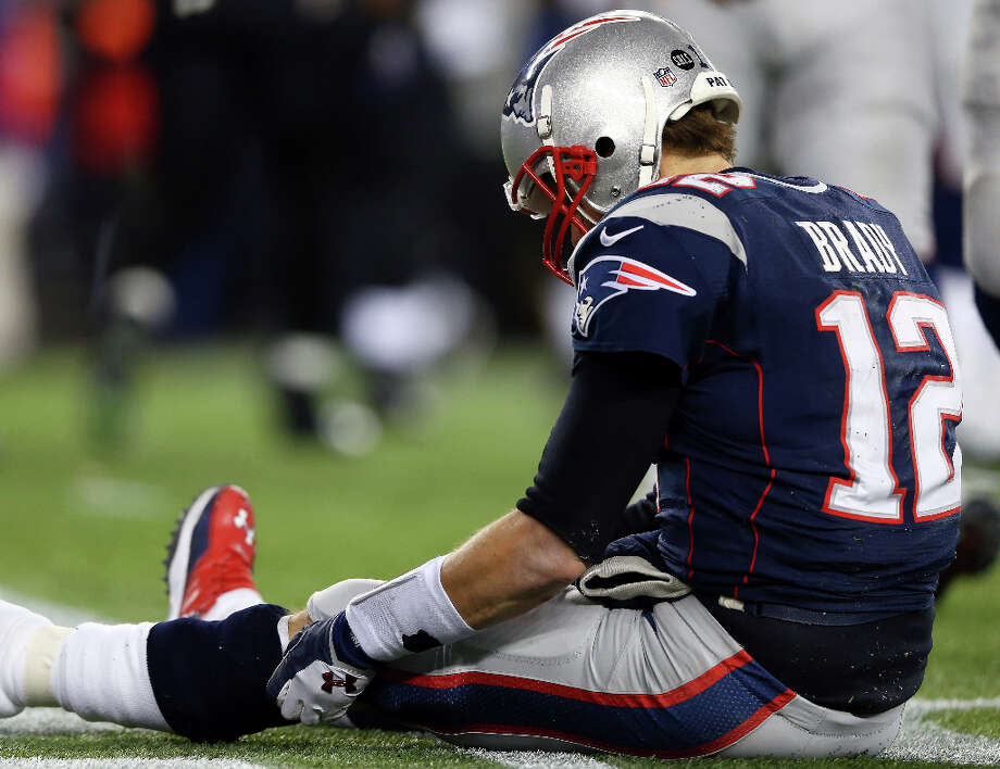 Tom Brady #12 of the Patriots sits on the ground after getting knocked down. Photo: Elsa, Getty Images / 2013 Getty Images