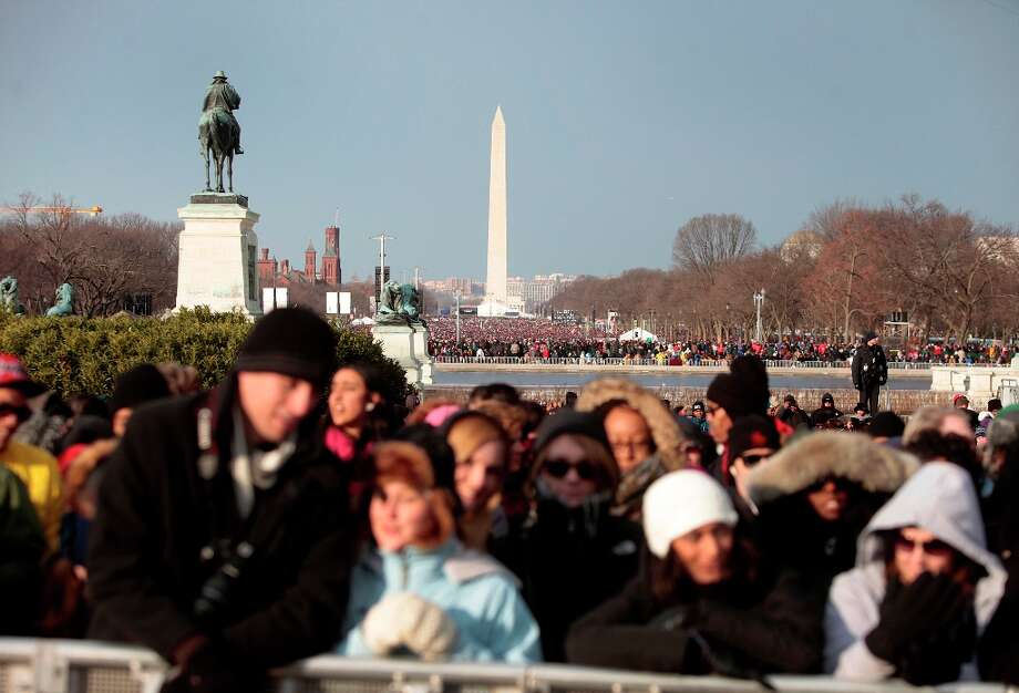The Washington monument stands in the distance as attendees gather before the start of the U.S. presidential inauguration in Washington, D.C., U.S., on Monday, Jan. 21, 2013. As he enters his second term, President Barack Obama has shed the aura of a hopeful consensus builder determined to break partisan gridlock and adopted a more confrontational stance with Republicans. Photo: Victor J. Blue, Bloomberg / © 2013 Bloomberg Finance LP