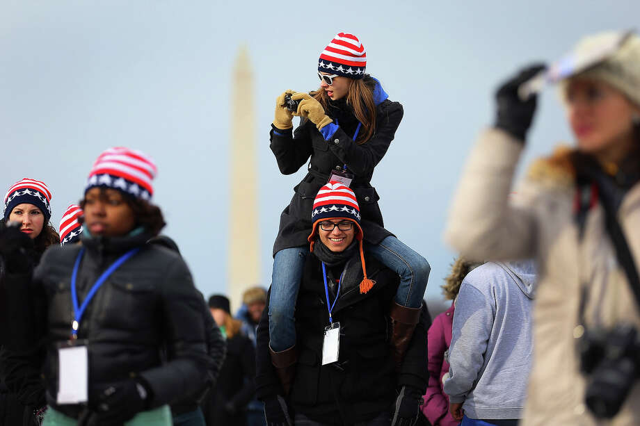 WASHINGTON, DC - JANUARY 21: Sydney Yochum sits on the shoulders of Luis Lauro Lopez near the U.S. Capitol building on the National Mall as they and others wait for the start of the Inauguration ceremony on January 21, 2013 in Washington, DC.  U.S. President Barack Obama will be ceremonially sworn in for his second term today. Photo: Joe Raedle, Getty Images / 2013 Getty Images