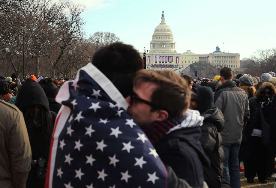 WASHINGTON, DC - JANUARY 21: Gustavo Cinfuentes (L) and Greg Josken hug near the U.S. Capitol building as they stand on the National Mall waiting for the start of the Inauguration ceremony on January 21, 2013 in Washington, DC.  U.S. President Barack Obama will be ceremonially sworn in for his second term today. Photo: Joe Raedle, Getty Images / 2013 Getty Images