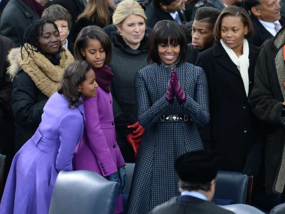 Michelle Obama, with Sasha(L), Malia(C), wears a Thom Browne coat and colorful gloves for President Barack Obama's 57th Presidential Inauguration ceremonial swearing-in at the US Capitol on January 21, 2013 in Washington, DC.  Photo: STAN HONDA, AFP/Getty Images / AFP