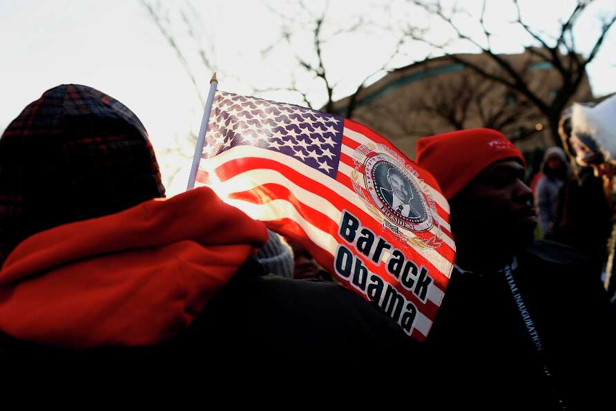 An attendee holds an American flag with an image of President Barack Obama before the start of the U