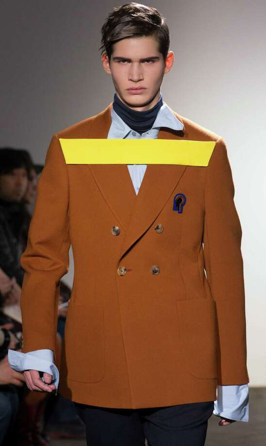 He threw a tantrum because he hates the brown coat, so they had to tape it on. He did, however, win the battle against rolling up his sleeves. A model wears a creation by Belgian fashion designer Raf Simons fashion house Men's Spring-Summer 2013 collection, for Paris Fashion Week. Photo: Jacques Brinon, Associated Press / AP
