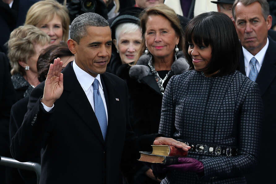President Barack Obama is sworn in during the public ceremony as First lady Michelle Obama looks on
