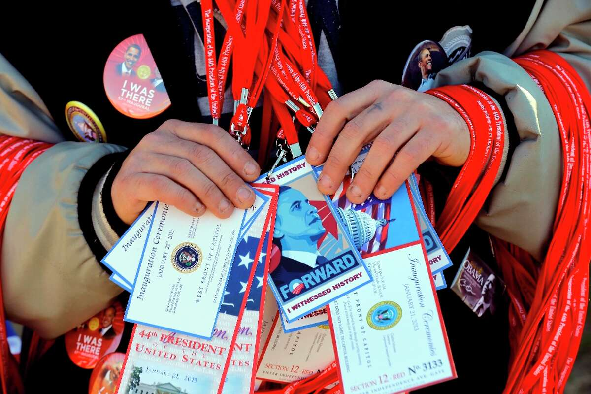 A vendor holds items for sale on the National Mall with the U.S. Capitol prepared for the ceremonial swearing-in of President Barack Obama, the 57th Presidential Inaugural, Sunday, Jan. 20, 2013 in Washington.