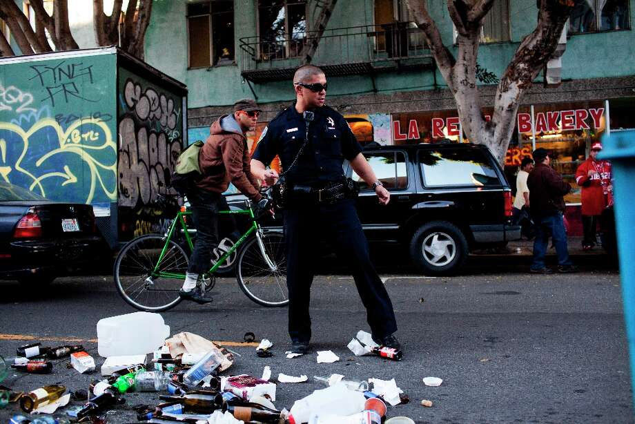 A SFPD officer swept broken glass out of the street after a fan threw a trash can into the middle of 24th Street during celebrations after the San Francisco 49er's beat the Atlanta Falcons and was promptly arrested by SFPD in San Francisco, Calif., Sunday, January, 20, 2013. Photo: Jason Henry, Special To The Chronicle / ONLINE_YES