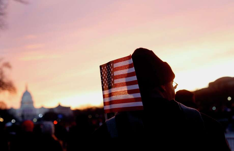 An attendee holds an American flag as the sun rises before the start of the U.S. presidential inaugu