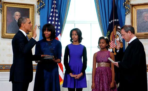 President Barack Obama is officially sworn-in by Chief Justice John Roberts in the Blue Room of the White House during the 57th Presidential Inauguration in Washington, Sunday, Jan. 20, 2013. Next to Obama are first lady Michelle Obama, holding the Robinson Family Bible, and daughters Malia and Sasha. Photo: LARRY DOWNING, Associated Press / Pool Reuters