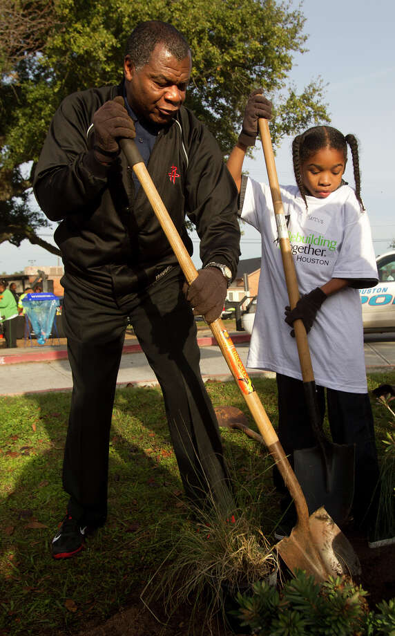 Former Houston Rocket Calvin Murphy, left, helps Marcus Chenier, 9, right, plant a tree at M. E. Foster Elementary School, Monday, Jan. 21, 2013, in Houston. Rebuilding Together Houston and NBA Cares partnered to help revitalize the Foster Place community as part of the 2013 Martin Luther King, Jr. Day of Service. The event included community cleanup, landscaping, and tree planting at Foster Place Elementary School and throughout the neighborhood. Photo: Cody Duty, Houston Chronicle / © 2012 Houston Chronicle