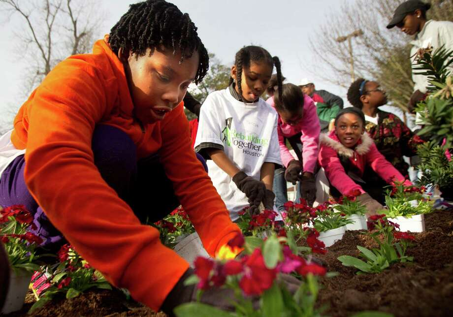 Erykah Moore, 10, left, plants flowers as she and other volunteers with NBA Cares and Rebuilding Together Houston plant trees at M. E. Foster Elementary School, Monday, Jan. 21, 2013, in Houston.  Photo: Cody Duty, Houston Chronicle / © 2012 Houston Chronicle