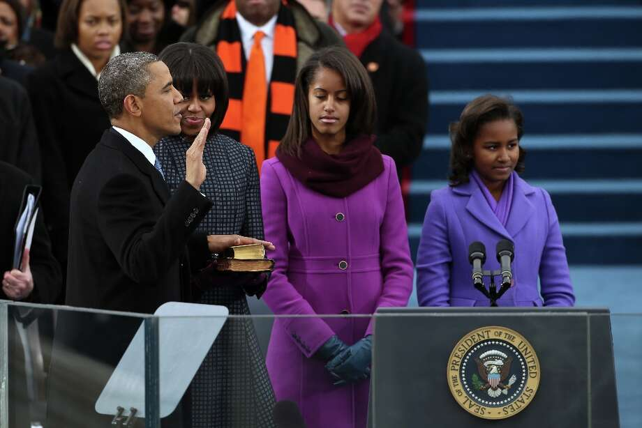 U.S. President Barack Obama is sworn in during the public ceremony as First lady Michelle Obama, and daughters, Sasha Obama (R) and Malia Obama look on during the presidential inauguration on the West Front of the U.S. Capitol January 21, 2013 in Washington, DC. Barack Obama was re-elected for a second term as President of the United States. Photo: Justin Sullivan, Getty Images / 2013 Getty Images