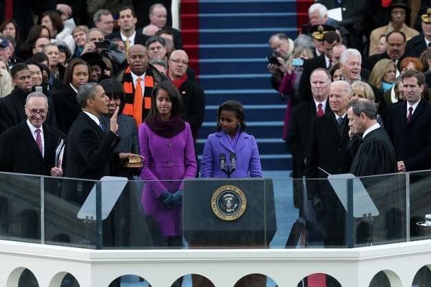 U.S. President Barack Obama is sworn in by Supreme Court Chief Justice John Roberts during the public ceremony as First lady Michelle Obama, and daughters, Sasha Obama (R) and Malia Obama look on during the presidential inauguration on the West Front of the U.S. Capitol January 21, 2013 in Washington, DC. Barack Obama was re-elected for a second term as President of the United States. Photo: Justin Sullivan, Getty Images / 2013 Getty Images