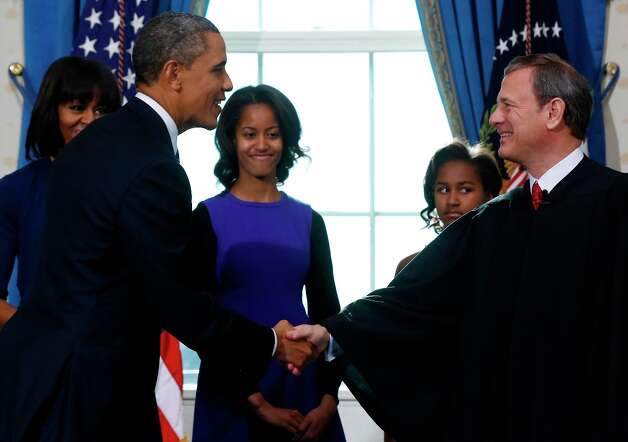 President Barack Obama shakes hands with Chief Justice John Roberts after Obama was officially sworn-in in the Blue Room of the White House during the 57th Presidential Inauguration in Washington, Sunday, Jan. 20, 2013, as first lady Michelle Obama and daughters Malia and Sasha watch. Photo: LARRY DOWNING, Associated Press / Pool Reuters