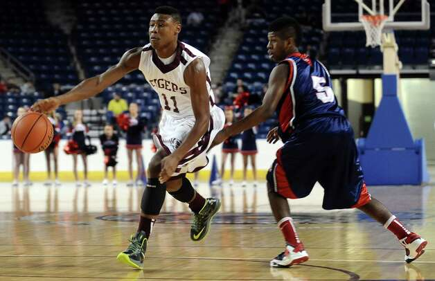 Silsbee player Jordan Holmes, #11, drives around HJ player Sammy Mitchell, #5, during the Silsbee High School boys basketball game against Hardin Jefferson High School on Tuesday, January 15, 2013, at Ford Arena in Beaumont. Photo taken: Randy Edwards/The Enterprise