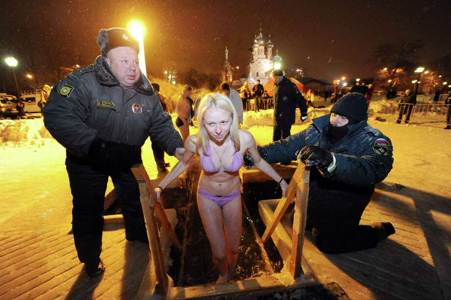 This picture taken late on January 18, 2013 shows Russian police helping a Russian Orthodox believer to take a bath in the ice cold water of a pond  in Moscow to mark Epiphany celebrations.        AFP PHOTO / ANDREY SMIRNOV        (Photo credit should read ANDREY SMIRNOV/AFP/Getty Images) Photo: ANDREY SMIRNOV, Multiple / 2013 AFP