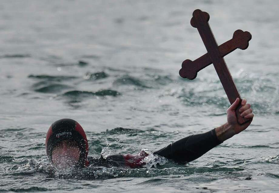 A Romanian diver shows a wooden cross he retrieved from the Black Sea thrown by an Orthodox priest during an epiphany religious service in Constanta city Jan. 6. (DANIEL MIHAILESCU/AFP/Getty Images) Photo: DANIEL MIHAILESCU, Multiple / 2013 AFP