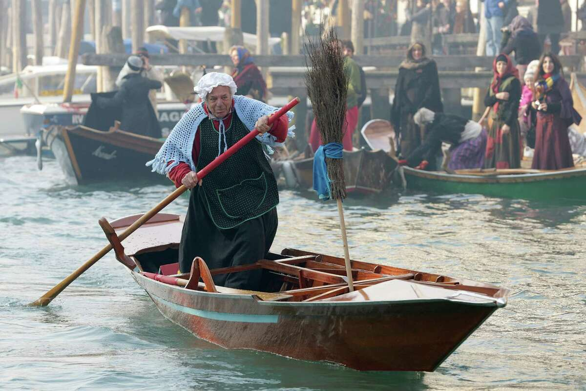 A participant dressed as 'Befana' rows on Gran Canal during the traditional Epiphany Boat Race on Jan. 6 in Venice, Italy. In Italy, Epiphany is celebrated on Jan. 6, and on the canal mascareta boats are piloted in tribute to 'Befana', a witch who delivers gifts and sweets to children. (Photo by Barbara Zanon/Getty Images)