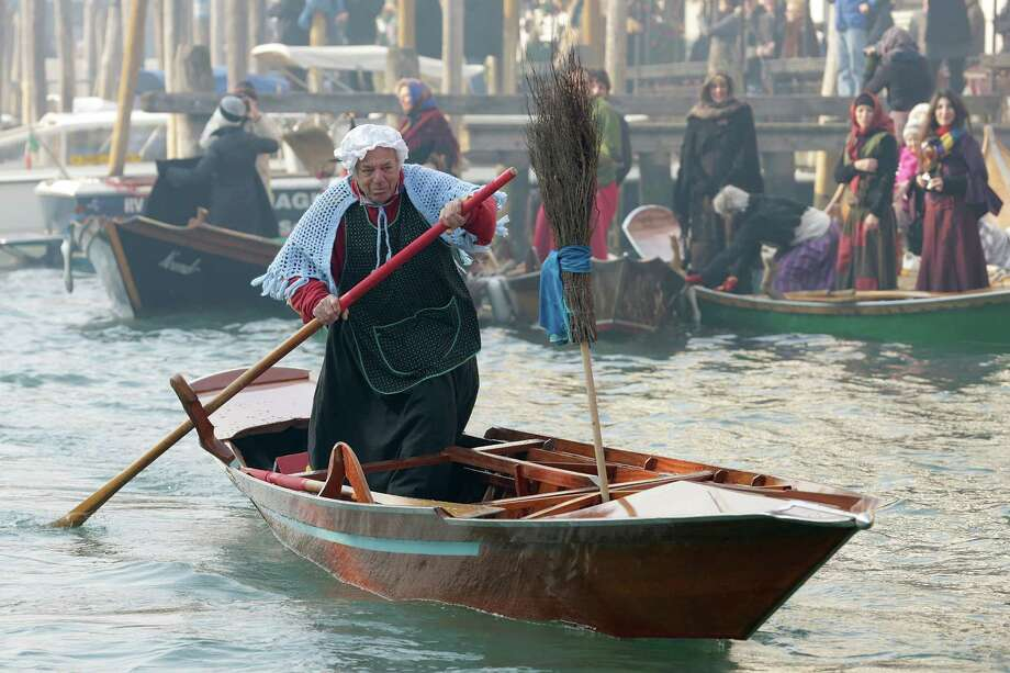 A participant dressed as 'Befana' rows on Gran Canal during the traditional Epiphany Boat Race on Jan. 6 in Venice, Italy. In Italy, Epiphany is celebrated on Jan. 6, and on the canal mascareta boats are piloted in tribute to 'Befana', a witch who delivers gifts and sweets to children. (Photo by Barbara Zanon/Getty Images) Photo: Barbara Zanon, Multiple / 2013 Barbara Zanon