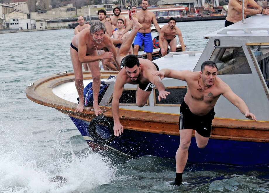 Greek Orthodox swimmers compete to retrieved the wooden cross from the Bosphorus river's Golden Horn after a mass as part of celebrations of the Epiphany day at the Church of Fener Orthodox Patriarchiate in Istanbul on Jan. 6. (BULENT KILIC/AFP/Getty Images) Photo: BULENT KILIC, Multiple / 2013 AFP