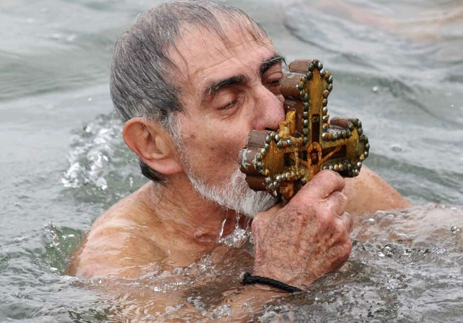 A Greek Orthodox swimmer kisses the wooden cross he rtrieved from the Bosphorus river's Golden Horn. (BULENT KILIC/AFP/Getty Images) Photo: BULENT KILIC, Multiple / 2013 AFP