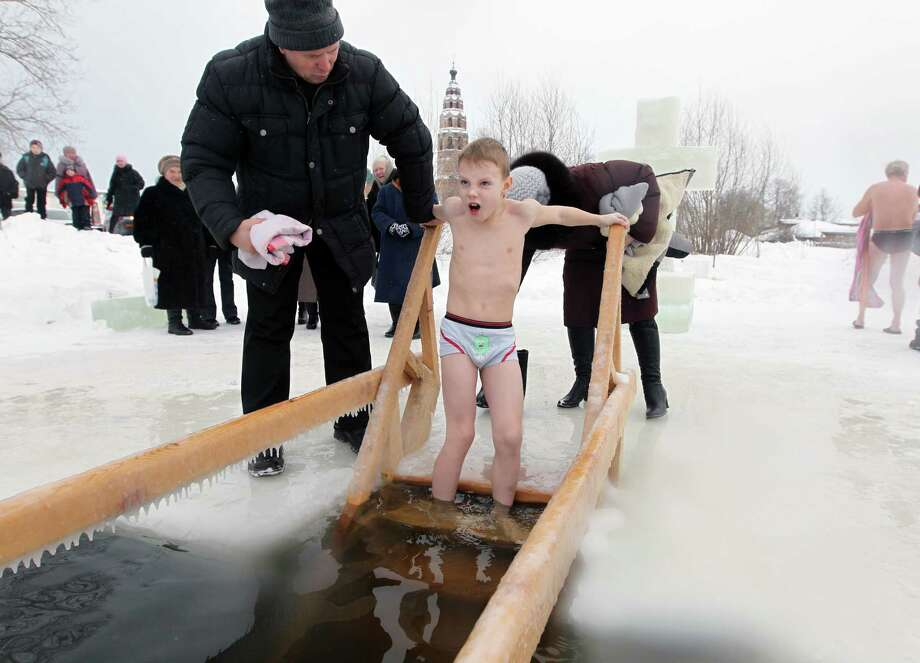 A young lad bathes in the icy-cold water of a lake during Orthodox Epiphany celebrations on Friday in the Yaroslavl region north of Moscow, Russia. (Photo by Sasha Mordovets/Getty Images) Photo: Sasha Mordovets, Multiple / 2013 Sasha Mordovets