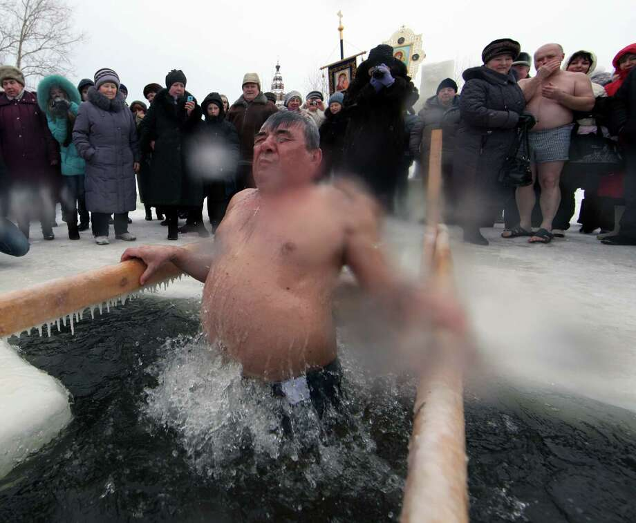 A Russian Orthodox bathes in the icy-cold water of a lake during Orthodox Epiphany celebrations on Friday in the Yaroslavl region, 260 km north of Moscow, Russia.  (Photo by Sasha Mordovets/Getty Images) Photo: Sasha Mordovets, Multiple / 2013 Sasha Mordovets