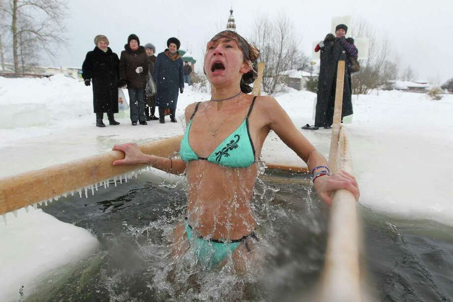 YAROSAVL, RUSSIA - JANUARY 19: A Russian Orthodox believer reacts to the water temperature during Orthodox Epiphany celebrations in the icy-cold water of the lake in Yaroslavl region, 260 km. North of Moscow on January, 19, 2013 in Russia.  People all over Russia are taking part in a baptism ceremony, one the biggest events in the Christian Orthodox calender. (Photo by Sasha Mordovets/Getty Images) Photo: Sasha Mordovets, Multiple / 2013 Sasha Mordovets