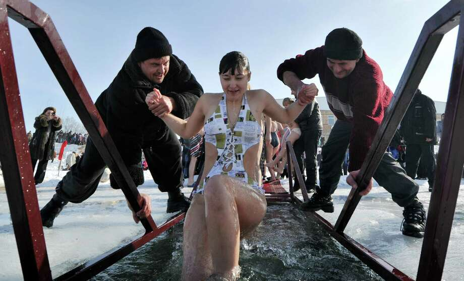 Assistants help an Orthodox believer to take a bath in the icy waters of a lake in the village of Leninskoe near Bishkek on Friday. (VYACHESLAV OSELEDKO/AFP/Getty Images) Photo: VYACHESLAV OSELEDKO, Multiple / 2013 AFP