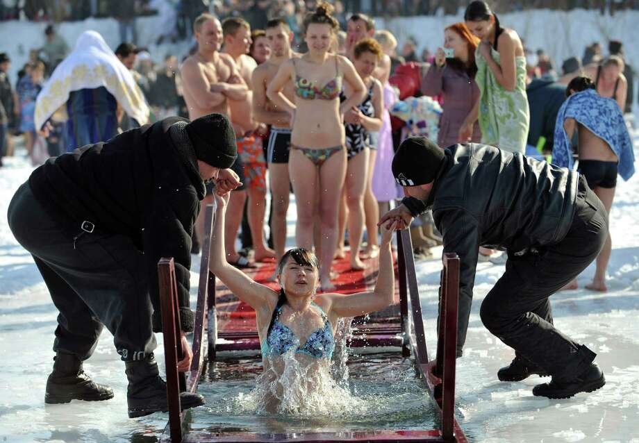 Assistants help an Orthodox believer to take a bath in the icy waters of a lake in the village of Leninskoe about 20km from Bishkek on Friday. (VYACHESLAV OSELEDKO/AFP/Getty Images) Photo: VYACHESLAV OSELEDKO, Multiple / 2013 AFP