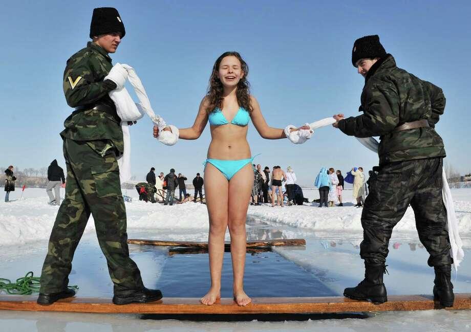 Assistants help an Orthodox believer to take a bath in the icy waters of a  lake in the village of Leninskoe about 20km from Bishkek on Saturday as part of Epiphany celebrations. (VYACHESLAV OSELEDKO/AFP/Getty Images) Photo: VYACHESLAV OSELEDKO, Multiple / 2013 AFP