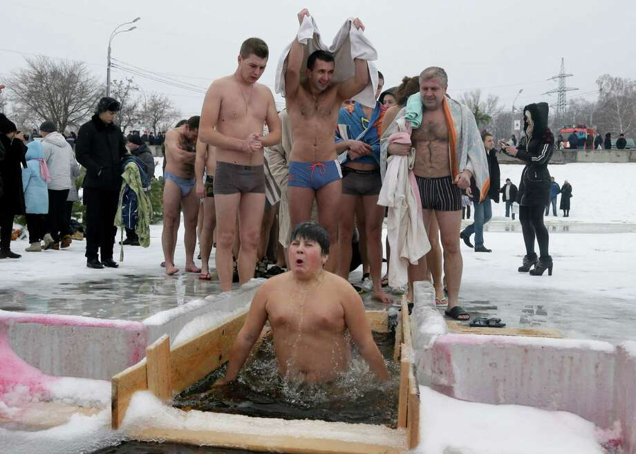 A boy jumps into an ice hole in the Dnipro River, as  others wait for their turn, as part of celebration of the Epiphany in the town of Vyshgorod outside the capital Kiev, Ukraine, on Saturday. (AP Photo/Efrem Lukatsky) Photo: Multiple