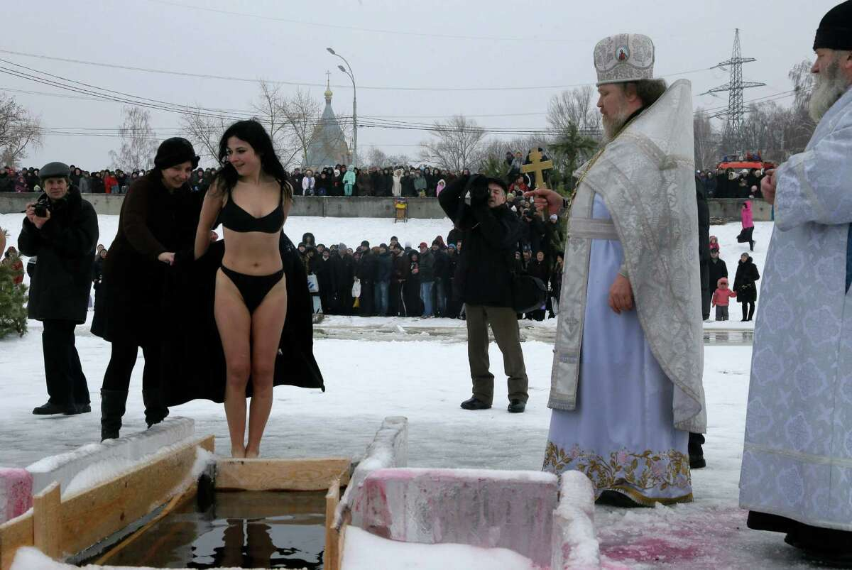 Bikinis weren't the only surprising images to come out of this years Epiphany celebrations around the world. Click through to see the other 29 images that might surprise you. In this photo, a priest blesses a woman before she jumps into an ice hole in the Dnipro River as part of celebration of the Epiphany in the town of Vyshgorod outside the capital Kiev, Ukraine, on Saturday. Orthodox believers celebrate the holiday of the Epiphany on Jan. 19, and traditionally bathe in holes cut through thick ice on rivers and ponds to cleanse themselves with water deemed holy for the day. (AP Photo/Efrem Lukatsky)
