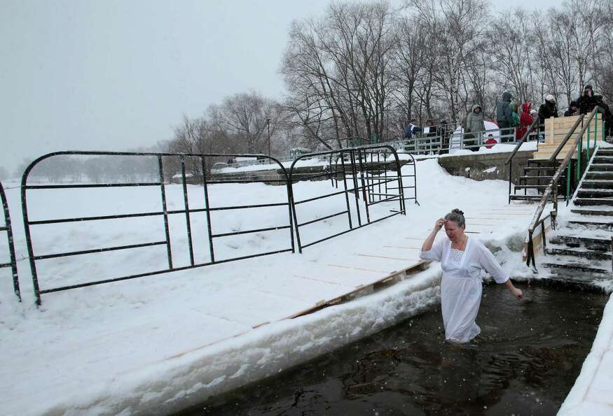 A woman crosses herself while bathing  in the ice cold water of the Moskva River, in Moscow, Russia,