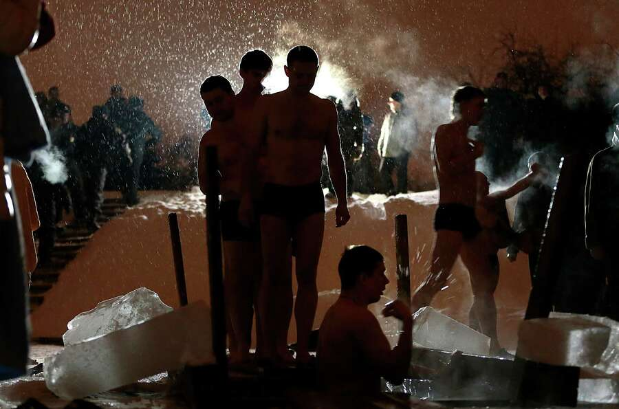People stand in a queue to the bath of the ice cold water as they take the bath in the ice hole of t