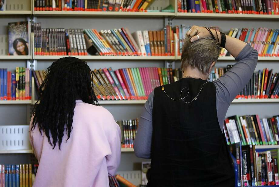 Amy Cheny mulls over what book to offer to a young girl based on her reading level and her interests at the Alameda County Juvenile Hall Library in San Leandro Calif.,  on August 24, 2011. These girls are between the ages of 16-18 and through Cheny's reading program are encouraged to improve their reading ability and enjoy the books they check out. Photo: Audrey Whitmeyer-Weathers, The Chronicle