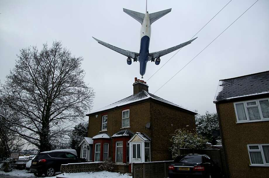A plane flies over a residential area to land at Heathrow airport in west London on January 21, 2013 after the airport announced further flight cancellations due to adverse weather. London's Heathrow Airport warned of further flight cancellations on January 21 which would leave thousands more passengers stranded on the fourth day of delays after heavy snow swept across Britain. Photo: Andrew Cowie, AFP/Getty Images