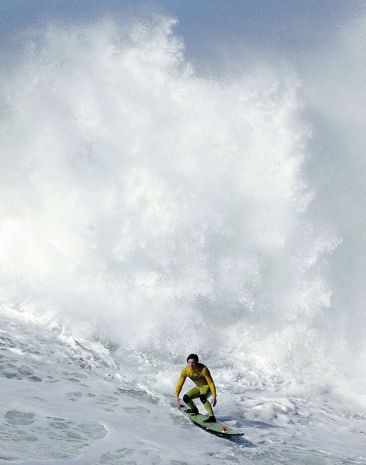 Don't look back:Colin Dwyer ignores the house-sized wave of whitewater chasing him at Mavericks in Half Moon Bay, Calif. Photo: Marcio Jose Sanchez, Associated Press