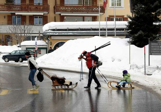 A man and woman pull two children across a pedestrian crossing as they sit on wooden sledges in Klosters, Switzerland, on Monday, Jan. 21, 2013. This week the business elite gathers in the Swiss Alps for the 43rd annual meeting of the World Economic Forum in Davos, the five day event runs from Jan. 23-27. Photographer: Chris Ratcliffe/Bloomberg Photo: Chris Ratcliffe, Bloomberg / Copyright 2013 Bloomberg Finance LP, All Rights Reserved.