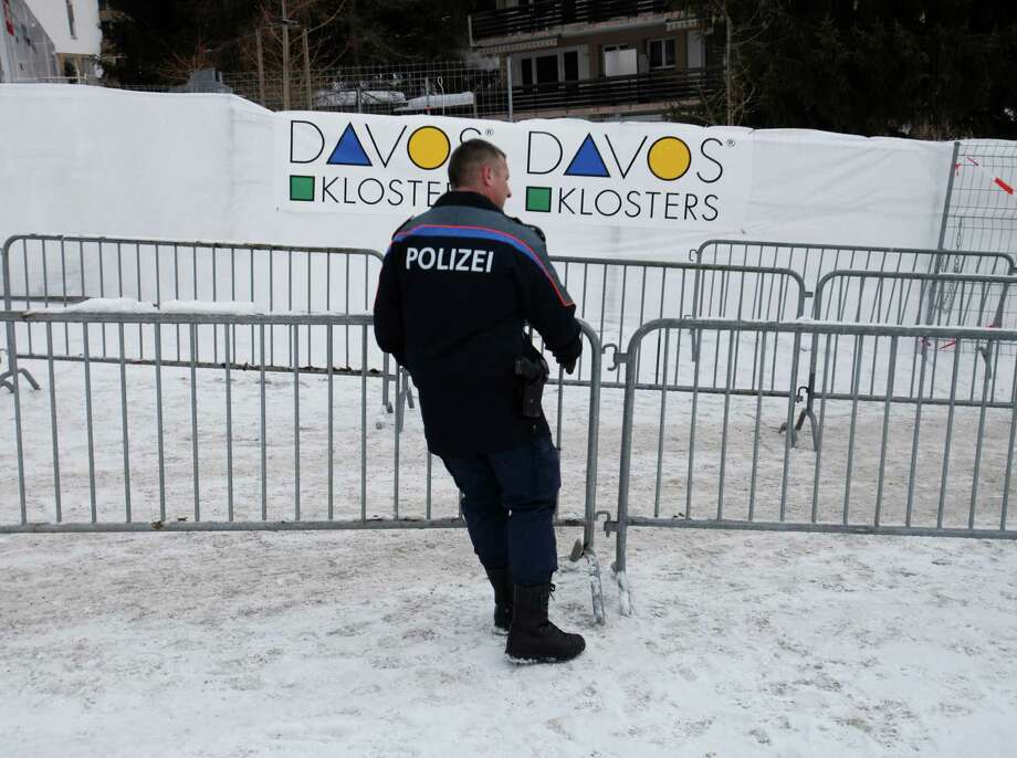 A member of the Swiss police force moves a security barrier into position outside the Congress Centre ahead of the World Economic Forum (WEF) meeting in Davos, Switzerland, on Monday, Jan. 21, 2013. This week the business elite gathers in the Swiss Alps for the 43rd annual meeting of the World Economic Forum in Davos, the five day event runs from Jan. 23-27. Photographer: Simon Dawson/Bloomberg Photo: Simon Dawson, Bloomberg / Copyright 2013 Bloomberg Finance LP, All Rights Reserved.