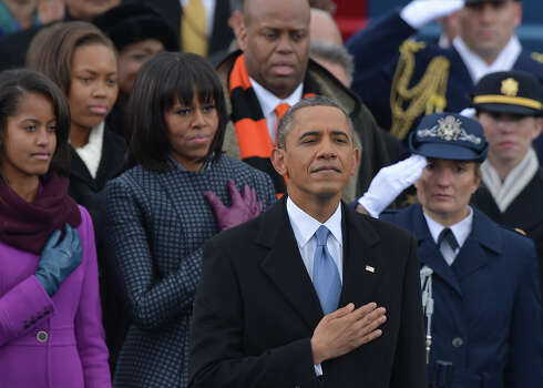 US President Barack Obama, surrounded by members of his family, listens to the National Anthem during the 57th Presidential Inauguration ceremonial swearing-in at the US Capitol on January 21, 2013 in Washington, DC.   AFP PHOTO/Jewel Samad Photo: JEWEL SAMAD, AFP/Getty Images / 2013 AFP