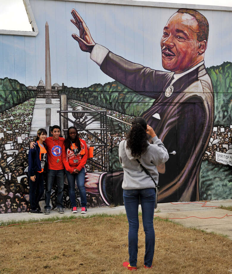 Brianna Gutierrez, Ben Pelayo and Kayani Spriggs have their picture taken in front of a Martin Luther King mural by Rossevelt High School classmate Alessandra Jefferson Monday before the MLK March. Photo: Robin Jerstad