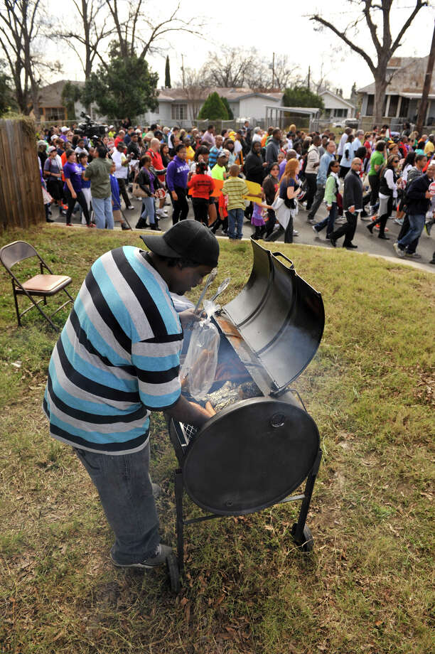 Fred Jefferson cooks sausage and turkey legs as thousands walk by during the MLK March Monday. Photo: Robin Jerstad