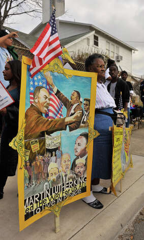 Clara Hunt holds a sign to honor Dr. Martin Luther King as she watches the MLK March Monday morning. Photo: Robin Jerstad