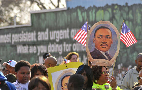 Robbie Thompson holds a sign honoring Dr. Martin Luther King prior to the start of the MLK March Monday. Photo: Robin Jerstad
